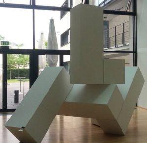 Zu diesem Kunst-Werk gibt es ein Tastobjekt. Das Tastobjekt darf berührt werden. Das Kunst-Werk hat der Künstler Herbert Höcky im Jahr 2013 aus Sperrholz gefertigt. Er hat das Sperrholz mit weißer Farbe angestrichen und mattiert. Deshalb hat die weiße Farbe keinen Glanz. Aus dem Sperrholz hat der Künstler längliche Schachteln gebaut. Sie stehen nebeneinander und übereinander. Alle Schachteln zusammen bilden eine neue Form. Man kann sie von allen Seiten aus ansehen. Die Schachteln sehen wie schwere Beton-Steine aus. Das kommt durch die matte Farbe. Trotzdem wirkt die Skulptur so, als könnte man sie bewegen. Sehen Sie die Schachtel ganz oben? Sie steht auf der Kante einer anderen Schachtel. Man kann auch sagen, sie steht auf einem Grat, also auf einem schmalen Weg. Dadurch wirkt das Kunst-Werk nicht stabil. Man fragt sich: Fällt die Schachtel gleich runter? Vielleicht hat das Kunst-Werk diese Bedeutung: Manchmal stehen wir Besucherinnen und Besucher auch auf einem schmalen Grat. Dann fragen wir fragen uns: Können wir auf diesem Grat wandern oder stürzen wir vielleicht ab?