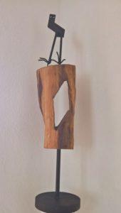 Dieses Kunstwerk dürfen sie berühren. Das Kunst-Werk hat der Künstler Volker Wagner im Jahr 2001 gemacht. Es ist eine Skulptur aus Metall und Holz. Eine Skulptur ist eine Form oder eine Figur. Sie steht frei im Raum und man kann sie von allen Seiten aus ansehen. Diese Figur besteht aus 3 Teilen: Ganz oben sehen Sie ein dunkles Metall-Teil. Es ist wie ein Körper gebogen und hat oben 2 runde Löcher. Die Löcher erinnern an die großen Augen von Eulen. An den Metall-Körper sind 2 Metall-Stäbe mit Krallen geschweißt. Die Krallen halten sich auf einem großen Holz-Klotz fest. Der Holz-Klotz bildet den 2. Teil der Figur. Er ist mit einem Holzschnitz-Werkzeug bearbeitet. Deshalb ist er ganz glatt. In der Mitte hat der Künstler einen Teil von dem Holz-Klotz herausgeschnitten. Das wirkt wie die Öffnung einer Höhle. Die Metall-Figur und der Holz-Klotz sind auf einem Metall-Fuß befestigt. Er bildet den 3. Teil der Figur. Der Fuß besteht aus einem Metall-Stab und einer runden Boden-Platte. Der Künstler hat die Figur aus weggeworfenen Dingen gefertigt. Für die Menschen waren diese Dinge Müll. Aber für den Künstler sind diese Dinge wertvoll.