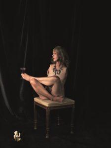 Hinter gekreuzten Beinen verbirgt sich der Körper einer anmutigen Frau. Sie sitzt auf einem Hocker. Ihr Blick geht in die Ferne. Ein schweres Collier lenkt den Blick des Betrachters weg von ihren fehlenden Armen. Dunkelblonde Haare umspielen ein zartes Gesicht. Mit den Zehen balanciert sie ein gefülltes Rotweinglas. Vor einem dunklen Hintergrund kniet ein Engel, der ihr