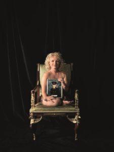 Das Kunst-Werk ist eine Fotografie auf Forex. Das ist eine leichte und stabile Holz-Platte. Blonde Engelslocken umrahmen das Gesicht einer Frau. Ihr Gesicht ist fein und zart und sie schaut direkt in die Kamera. Die Frau sitzt auf einem gepolsterten Stuhl mit Arm-Lehnen. Sie wirkt sehr klein auf dem Stuhl. Vor ihrem Oberkörper hält die Frau ein Foto. Auf dem Foto kann man einen Mann in Uniform erkennen. Das Foto verdeckt ihren nackten Oberkörper und ihre verkürzten Arme und Beine. Ihre helle Haut und ihr blondes Haar leuchten vor dem dunklen Hintergrund.