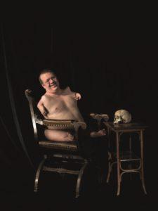 Das Kunst-Werk ist eine Fotografie auf Forex. Das ist eine leichte und stabile Holz-Platte. Auf einem alt-modischen Stuhl sitzt ein nackter Mann mit einer Brille. Seinen Körper hat er leicht zur Kamera gedreht. Man kann sehen, dass seine Arme und Beine verkürzt sind. Der Mann lacht in die Kamera und sein Gesicht wirkt entspannt. Rechts neben dem Stuhl steht ein kleiner Tisch mit schmalen Beinen und einer glatten Oberfläche. Auf der Oberfläche liegt ein Toten-Kopf. Der Toten-Kopf blickt mit seinen leeren Augen den Mann direkt an. Der scheint das nicht zu merken. So bilden das Lachen des Mannes und die Starre des Toten-Kopfs einen Gegensatz. Dieser Gegensatz macht das Bild spannend.