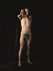 Bildbeschreibung: Nackt wie eine griechische Statue steht ein Mann vor dunklem Hintergrund. Neben seinem Gesicht hält er mit seinen verkürzten Armen eine Maske fest. Die Maske wirkt ausdruckslos- der Blick des Mannes dagegen entschlossen.