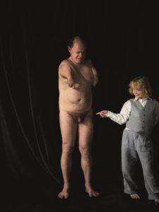 Bildbeschreibung: Stolz blickt der nackte Vater auf den bekleideten Sohn. Der Sohn trägt hellblaue Hose und Weste und ein weißes Hemd. Lächelnd lenkt er den Blick mit dem Zeigefinger zum Geschlechtsteil seines Vaters. Lächelnd amüsiert blickt sein Vater nach unten. Seine beiden Arme sind verkürzt und seine Finger kaum sichtbar. Vor dem dunklen Hintergrund offenbart das Bild eine harmonische Vater-Sohn Beziehung.