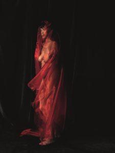 Geheimnisvoll - hinter einem fast durchsichtigen Schleier erkennt man eine Frauengestalt, schlank, groß mit einem verführerischen Seitenblick. Der Schleier gibt den Blick frei auf einen wohlgeformten Busen. Fast schwebend erscheint ihre Figur vor dem dunklen Hintergrund.
