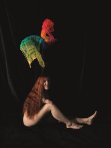 Das Kunst-Werk ist eine Fotografie auf Forex. Das ist eine leichte und stabile Holz-Platte. Eine sitzende Frau lächelt in die Kamera. Ein Bein hat sie ausgestreckt, das andere Bein hat sie aufgestellt. Sie hat ihren verkürzten rechten Arm auf das Knie abgelegt. Langes, rotes Haar verbirgt ihren Oberkörper. Man denkt, dass die Frau schwebt. Denn man sieht nur ihren feinen Körper und der Bild-Hintergrund ist ganz dunkel. Über der Frau schweben 2 Tücher in roter und grüner Farbe.