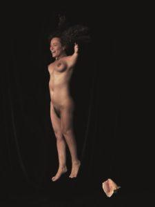 Das Kunst-Werk ist eine Fotografie auf Forex. Das ist eine leichte und stabile Holz-Platte. Eine schlanke Frau schwebt durch das Bild. Ihr Gesicht lacht und ihre Haare fliegen. Die verkürzten Arme hat sie in die Höhe gehoben. Sie strahlt viel Energie und Lebensfreude aus. Rechts neben ihren Füßen sieht man eine große Meeres-Muschel. Die Frau und die Meeres-Muschel leuchten vor dem dunklen Hintergrund.