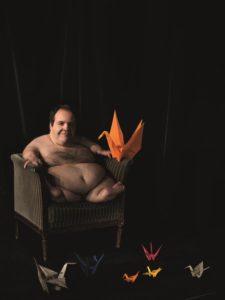 Das Kunst-Werk ist eine Fotografie auf Forex. Das ist eine leichte und stabile Holz-Platte. Ein dicker Mann sitzt in einem Sessel. Seine Arme und Beine sind stark verkürzt. Deshalb wirkt der Mann sehr klein. Seine verkürzten Arme hat er entspannt auf die Arm-Lehnen des Sessels gelegt. Und er schaut mit einem breiten Lächeln in die Kamera. Der Hintergrund des Fotos ist dunkel. Deshalb leuchten die Schwäne aus Papier auf dem Bild besonders bunt. Ein oranger Papier-Schwan sitzt direkt auf der Arm-Lehne neben dem Mann.