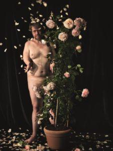 Das Kunst-Werk ist eine Fotografie auf Forex. Das ist eine leichte und stabile Holz-Platte. Ein Mann steht hinter einem blühenden Rosen-Strauch und blickt direkt in die Kamera. Seine linke Körper-Hälfte wird von dem Rosen-Strauch verdeckt. Trotzdem kann man sehen, dass sein Körper sehr kräftig ist. Sein rechter Arm ist gekrümmt und verkürzt. So wirken die Rosen-Blätter besonders zart. Einige liegen auf dem Boden, andere schweben um ihn herum. Die helle Haut des Mannes und die Rosen-Blätter leuchten vor dem dunklen Hintergrund.